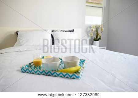 Healthy breakfast for two on a tray on a freshly made bed