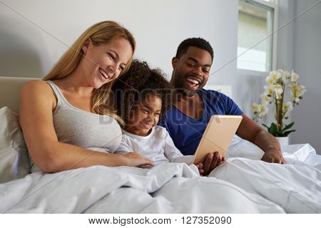 Mixed race couple and young daughter laugh in bed together