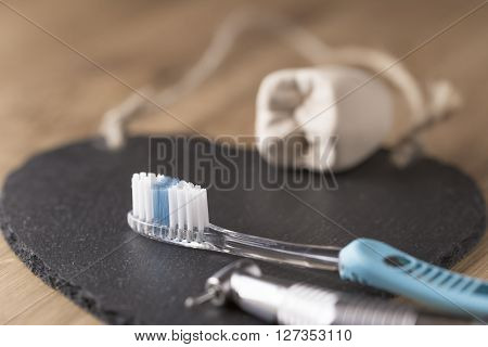 Two toothbrushes with a dentists drill and mold of tooth lying on a black mat with focus to the bristles of one brush in a dental and healthcare concept