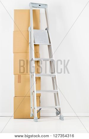Ladder with stack of moving carton boxes in front of white wall