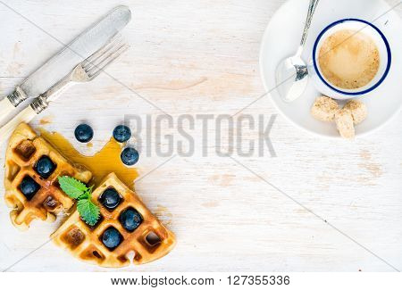 Espresso coffee cup and soft belgian waffles with fresh blueberries and marple syrup on white painted wooden board over light blue background. Top view, copy space, horizontal