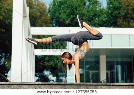 Young woman handstand yoga pose in urban environment