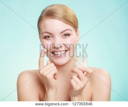 Woman Applying Cream On Her Skin Face.