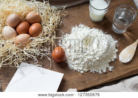 Flour, eggs and sheet of recipe on a wooden board in the kitchen