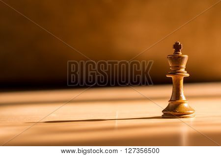 Single White King Chess Piece On Wood