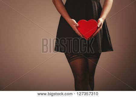 Beauty sexuality and seductiveness. Sexy part body woman wearing black dress and stockings panties holding red heart box present gift in hands. Studio shot.