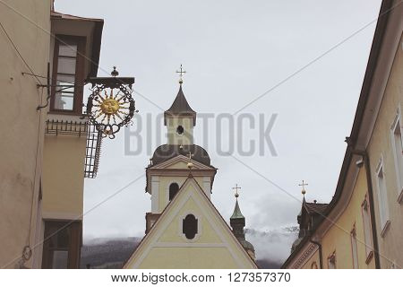 Church roof with bell tower and adjacent buildings with sign. Old church belfry with cross. Sun sign on the old building facade.