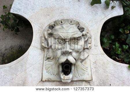 Marble water spring fountain. Italian potable water fountain. Fountain bas-relief surrounded with plants.