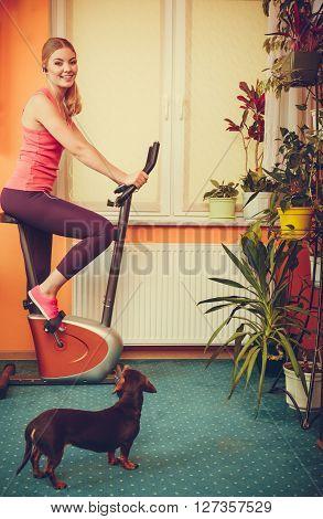 Woman On Exercise Bike Listening Music. Fitness