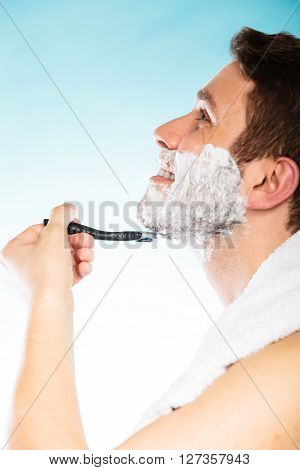Young Man Shaving Using Razor With Cream Foam.
