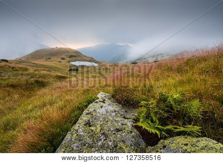 Foggy Mountain Landscape with a Tarn and Rocks in Foreground at Sunset