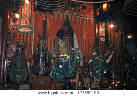 HONG KONG - CIRCA 1987: Sacred images stand on an altar in the Man Mo Miu Temple.