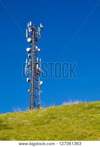 Tall Communication Tower On A Hill With Blue Sky
