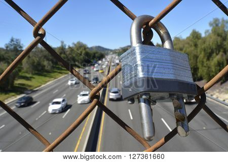Lock attached to fence over a freeway overpass with multiple cars in background