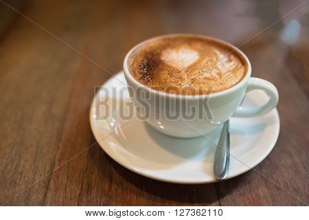 Hot coffee in white cup and saucer with silver spoon on wooden table in day time/ Hot coffee in white cup and saucer ** Note: Shallow depth of field