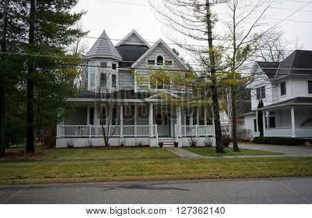 HARBOR SPRINGS, MICHIGAN / UNITED STATES - DECEMBER 23, 2015: A large home with a turret and a wraparound front porch on Second Street in Harbor Springs.