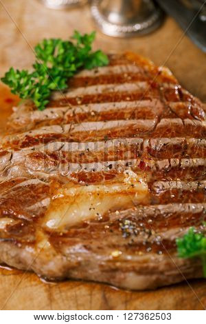 beef steak with vintage meat fork  on old wooden background