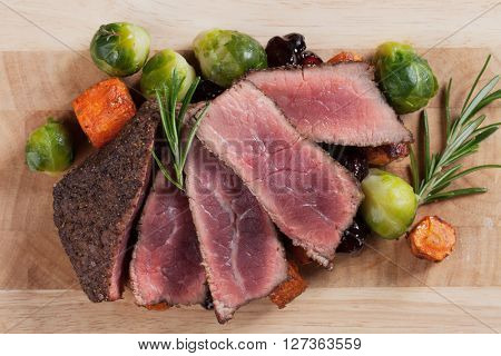 Rare beef steak, cut in slices, with carrot and brussel sprout