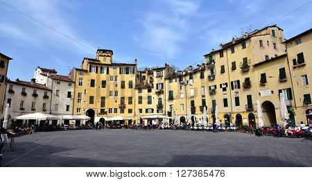 LUCCA, ITALY - APRIL 3: Piazza dell'Anfiteatro the most famous place in the historic center of Lucca built over an ancient roman amphitheater with its restaurants and bars  APRIL 3, 2016 in Lucca, Italy