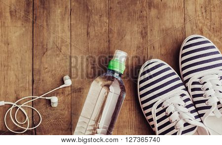 Shoes, water bottle and earphones. Healthy lifestyle, fitness. Concept of weight loss.