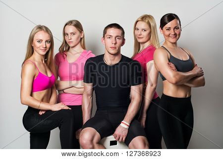 Fit group posing and smiling in studio.