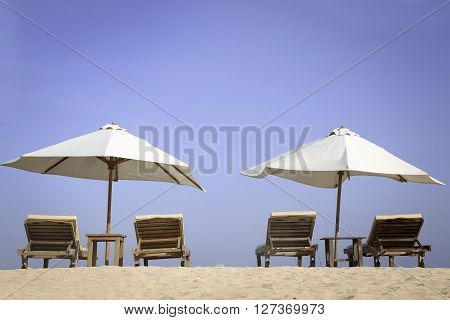 Tropical beach scenery with white parasols and chairs