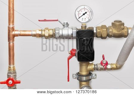 Heating system's cooper pipes with ball valves and manometer on a grey wall