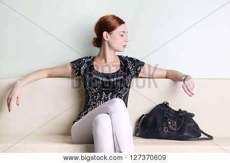 Young woman sitting and looking at her watch