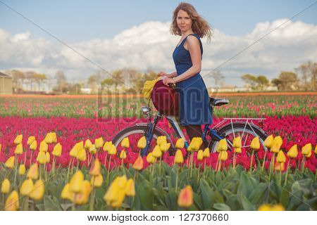 Happy female tourist in a blue dress standing with her bike in a spring field with yellow and pink  tulips