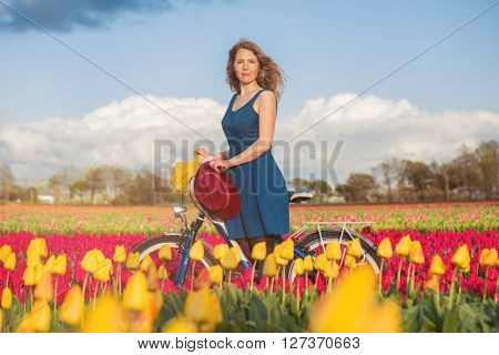Beautiful woman standing with her bicycle in a yellow and red tulips field at sunset.