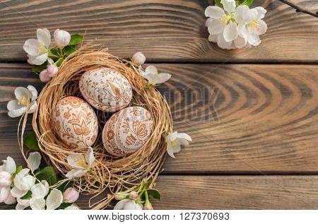 Nest with eggs on wooden background. Easter background.