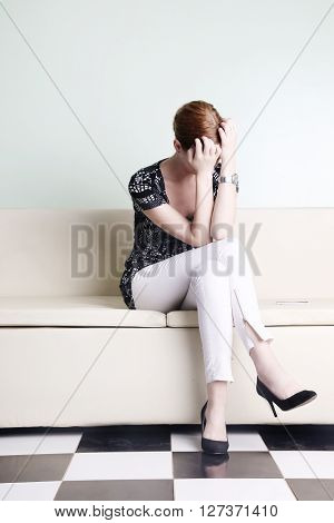 Young woman sitting with hands over her face, bored, worried or stressed