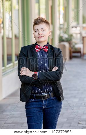 Dapper Gender Fluid Young Woman With Arms Crossed