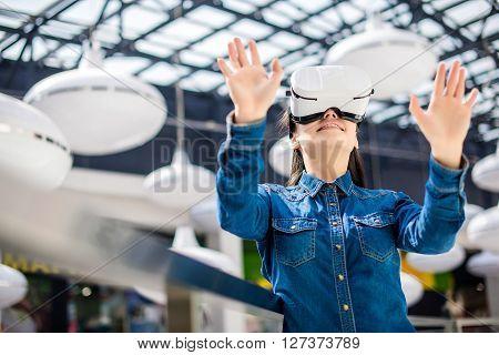 Emotional pretty woman wearing virtual reality glasses