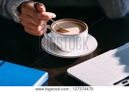 Woman holds hot cup of coffee, warming her hands, sat at a wooden table with laptop