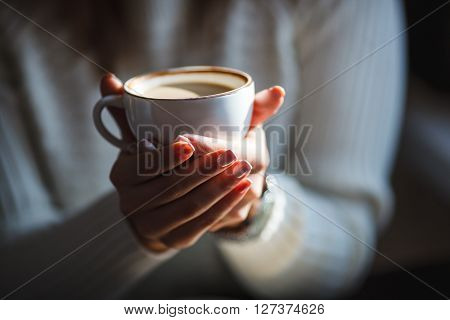 Woman holds hot cup of coffee, warming her hands, sat at a wooden table