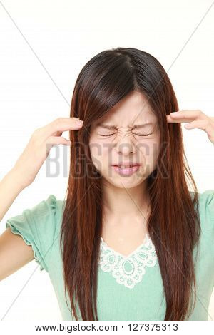 young Japanese woman suffers from headache on white background