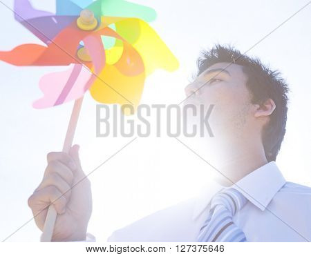 Businessman blowing pinwheel