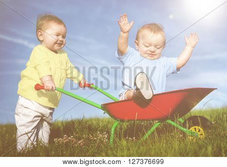 Two toddlers playing together outdoors.