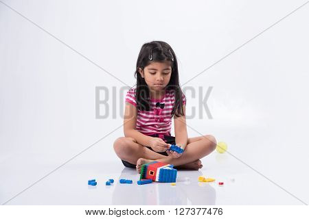 indian small girl or asian girl child playing with colourful blocks over white background, cute little indian girl constructing house with blocks, cute indian girl playing with toys