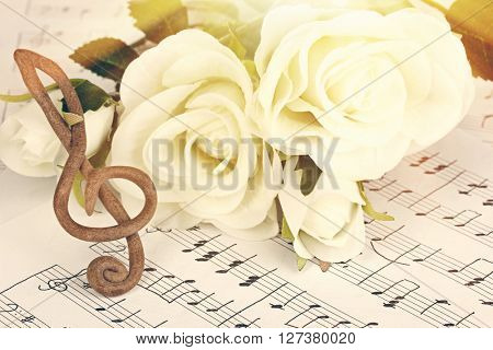 Treble clef and roses on music notes background. Retro style