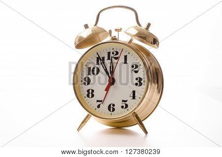 Old used golden alarm on a white background there is no more time to waste
