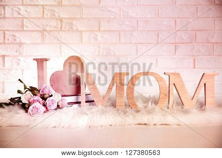 I love mom inscription made of wooden letters with heart on brick wall background