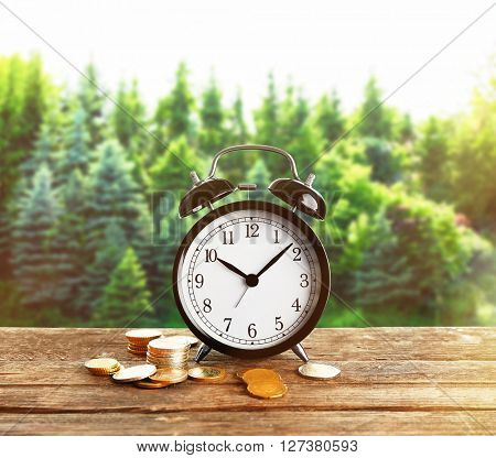 Alarm clock and money coins on wooden table, forest background
