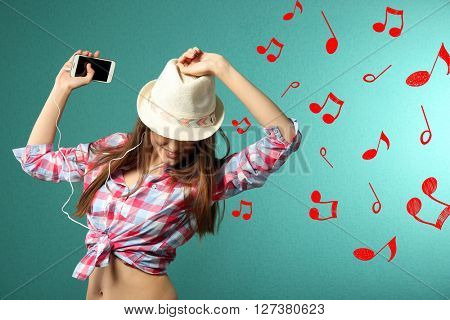 Young woman listening to music and dancing against turquoise background
