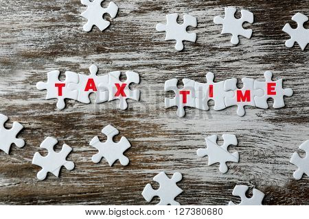 Tax Concept. White jigsaw puzzle with pieces on wooden background