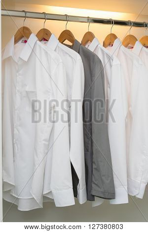 Row Of Shirts Hanging On Coat Hanger In White Wardrobe