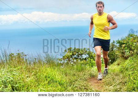 Running man runner living a healthy life active lifestyle. Male young athlete training cardio working out legs on a trail path in forest nature park and green grass in mountains with ocean background.