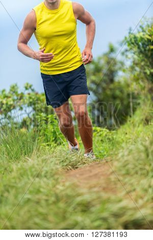 Man athlete running outside on a fitness trail run. Male runner jogging in sports shoes on grass path working out cardio in nature. Lower body crop for feet, legs, knees health pain challenge concept.