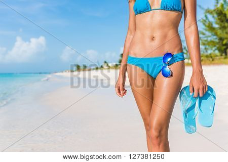 Sexy bikini body woman - abs, sunglasses, flip flops on beach vacation. Model showing slim abs and tanned skin on tropical caribbean travel destination vacation. Belly button stomach and thighs legs.